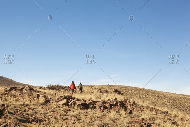 Two people hiking up a hill with rocky terrain