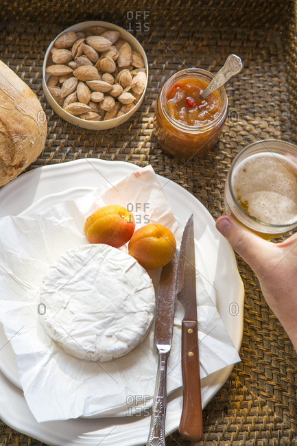 Camembert cheese with apricots, apricot chutney, almonds on a woven tray