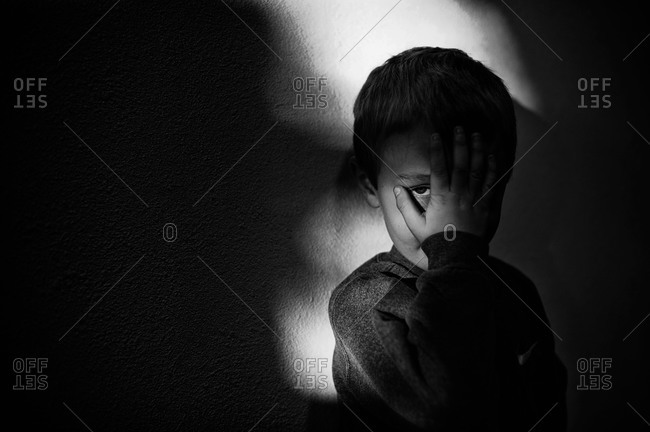 Young boy covering his face in a dark room