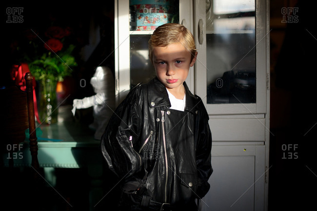 Young boy wearing a leather jacket