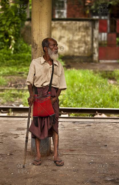 Yangon, Myanmar - August 16, 2011: Beggar waiting for the train, Yangon, Myanmar