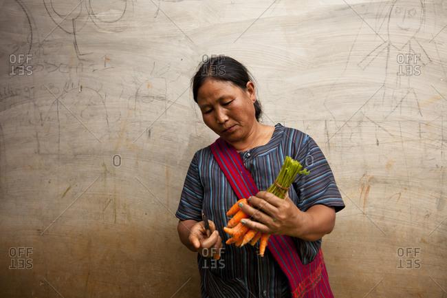 Yangon, Myanmar - August 19, 2011: Woman preparing carrots at market in Myanmar