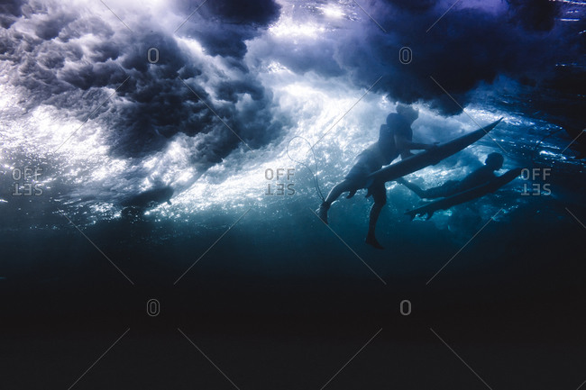 Two surfers diving under the incoming wave on Siargao Island, Philippines
