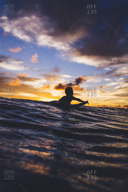 A surfer paddling in silhouette during a colorful sunset in the Philippines