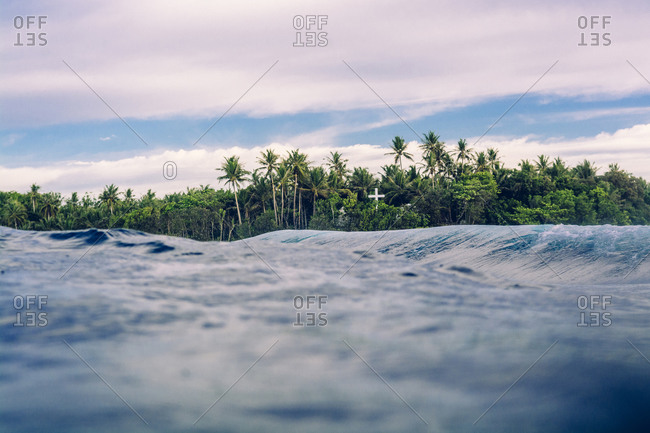 Cross in the jungle seen from the ocean. Siargao, Philippines