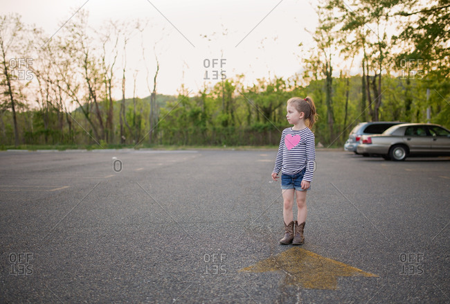 Girl standing in rural parking lot in summer