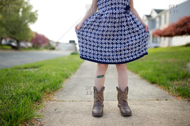 Girl standing on sidewalk holding out skirt