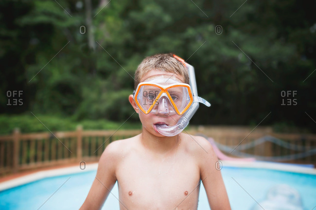 Portrait of boy in snorkel gear by pool