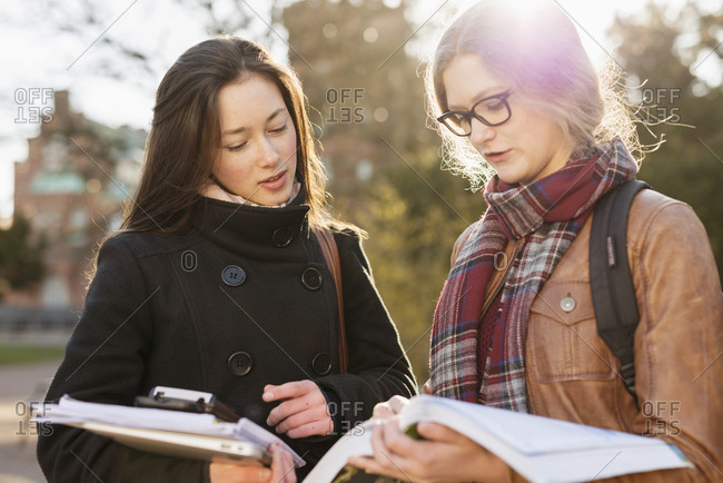 Two college students discussing textbook on campus quad