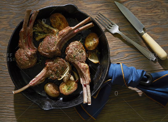 Overhead view of lamb chops in a cast iron skillet with potatoes