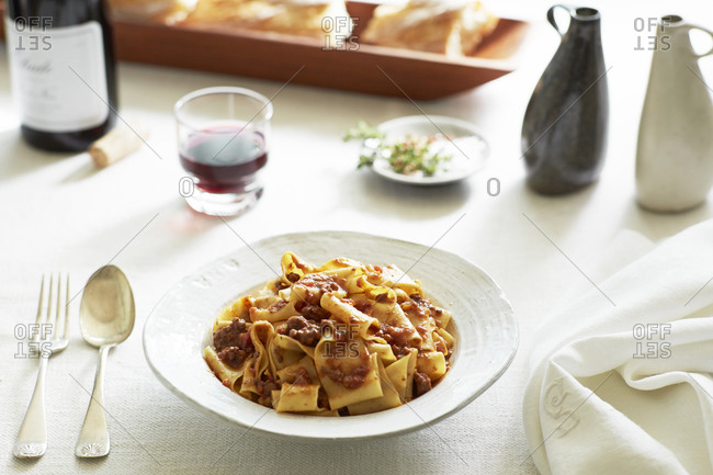 A dish of pasta on table with red wine and bread
