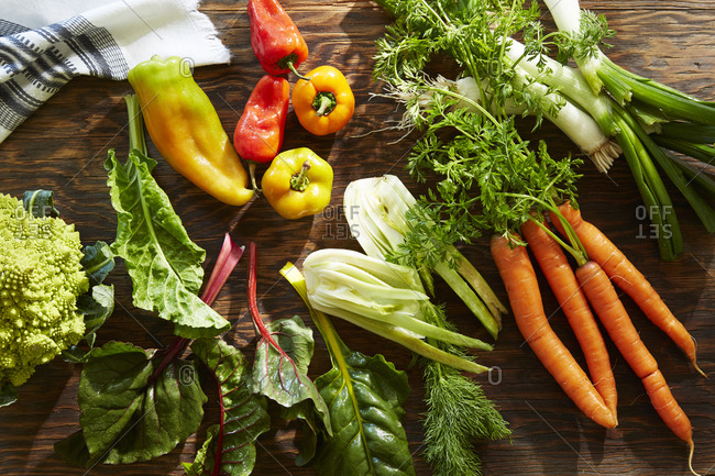 Overhead view of an arrangement of fresh vegetables on wooden board