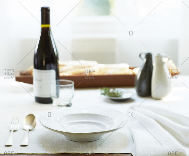 A simple but elegant table setting with a bottle of wine