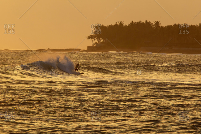 Surfing man at sundown, Bali