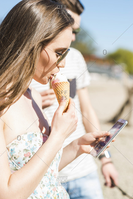 Young couple with ice cream cone and smartphone outdoors in summer