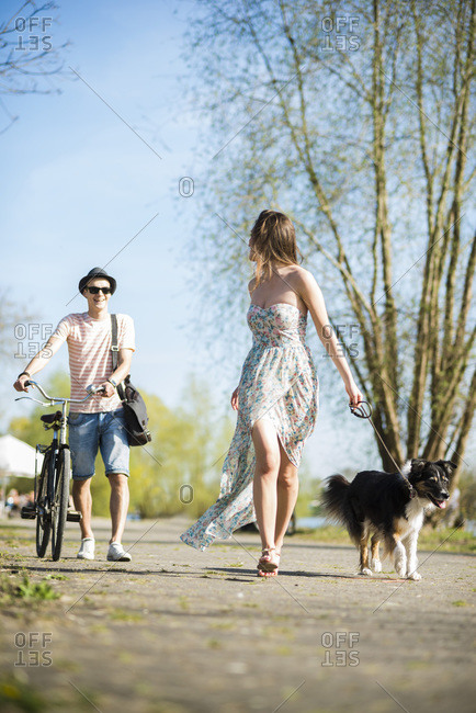 Young couple walking with dog outdoors in summer