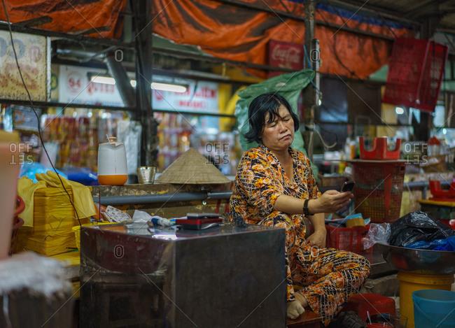 Saigon, Vietnam - November 15, 2014: Woman in market looking at cell phone