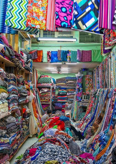 Saigon, Vietnam - November 15, 2014: Store attendant surrounded by fabric