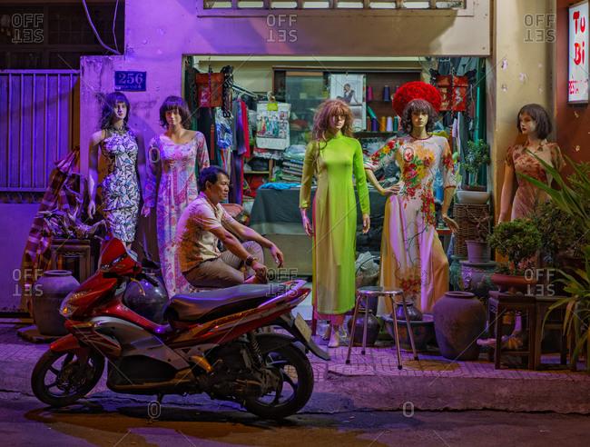 Saigon, Vietnam - November 16, 2014: Man on moped outside garment store
