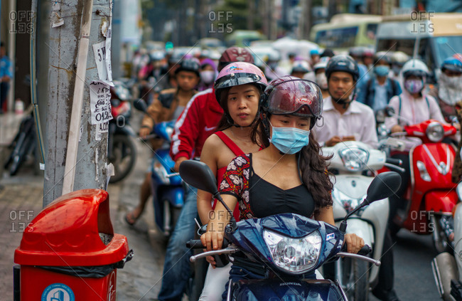 Saigon, Vietnam - November 17, 2014: People on a scooter wait in traffic
