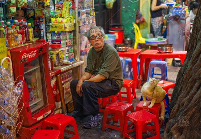 Hanoi, Vietnam - November 23, 2014: Market soda vendor looking at cat in Hanoi