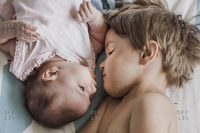Boy lying next to his baby sister