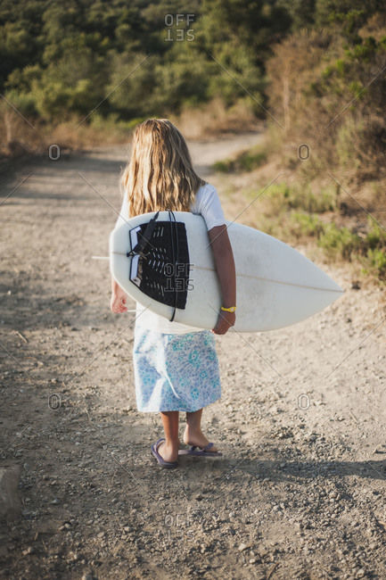 Back view of girl carrying a surfboard