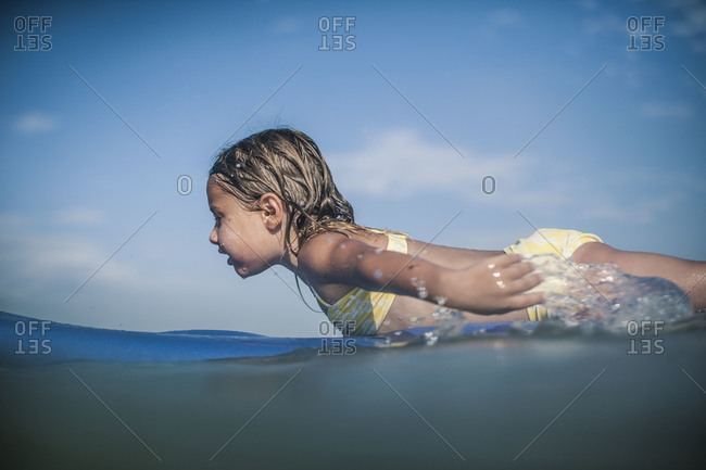 Young girl paddling on a surfboard