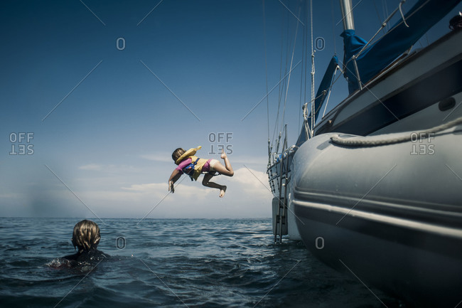 Young girl jumping into the ocean from a yacht