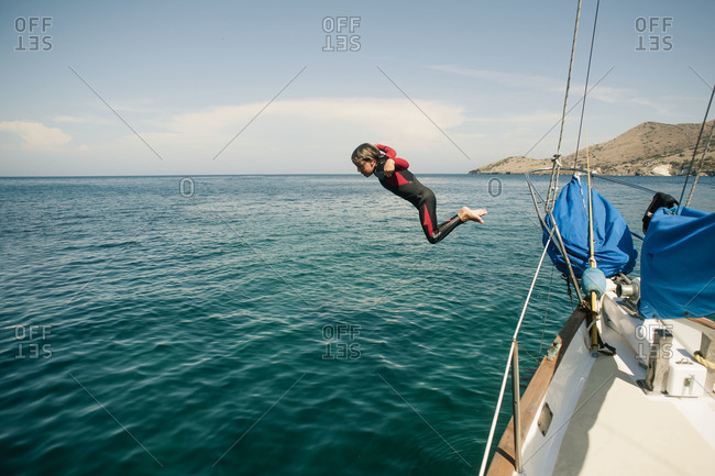 Young boy jumping into the ocean from a yacht
