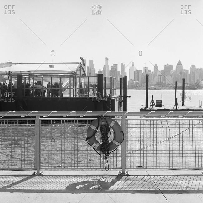 Ferry passengers waiting on dock overlooking city