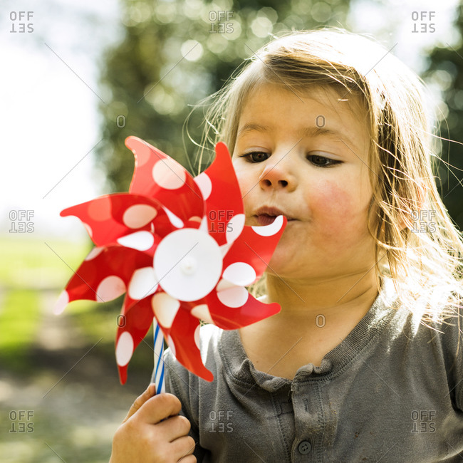 Young girl blowing on a pinwheel to make it turn