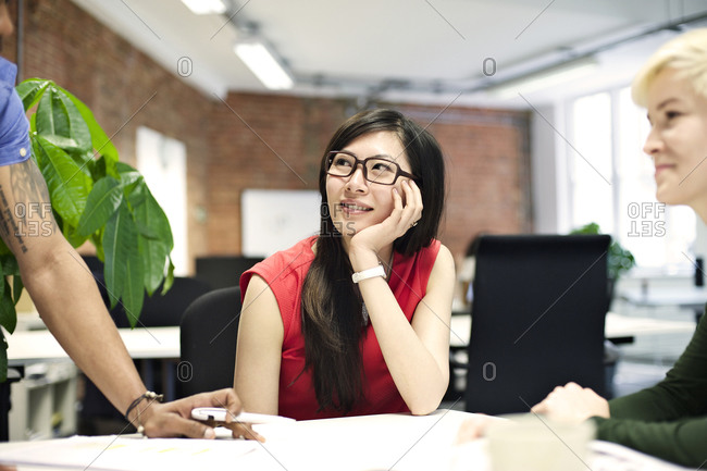 Young businesswoman listening to colleague