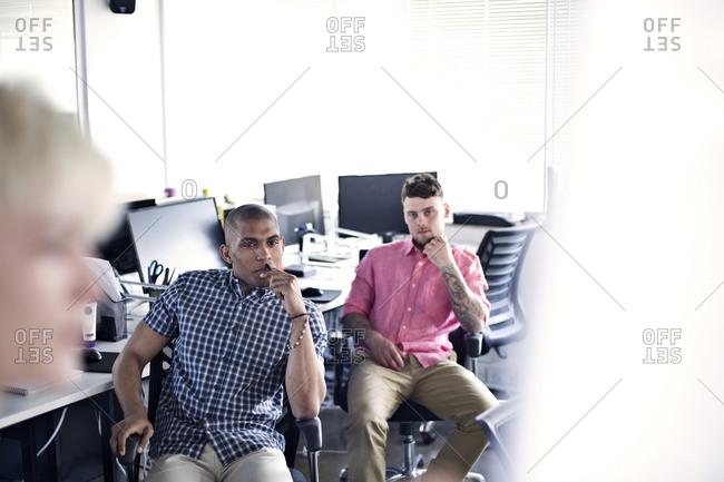 Businessmen listening to female colleague
