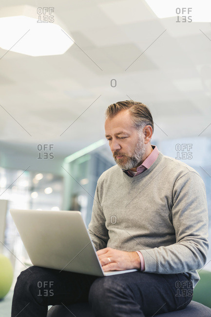 Businessman using laptop at modern office lobby