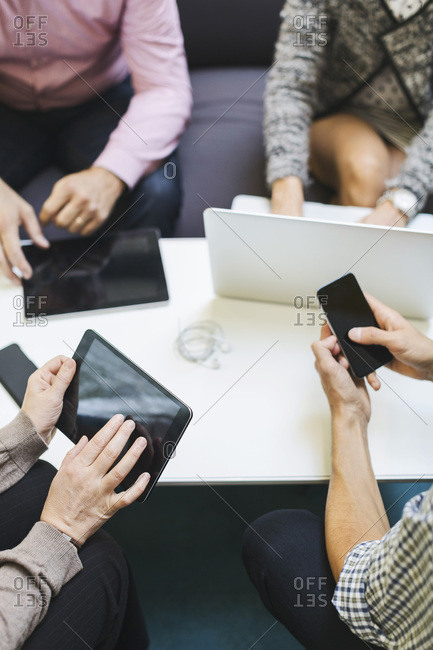 Midsection of businesspeople using technologies at table in office