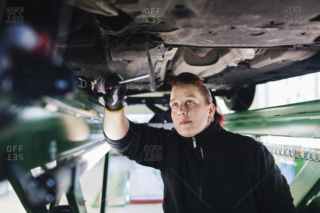 Female mechanic examining car with hammer in auto repair shop