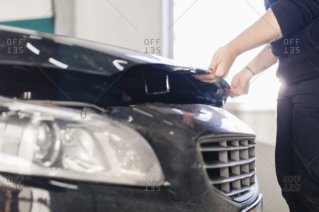 Midsection of mechanic opening car's hood in auto repair shop