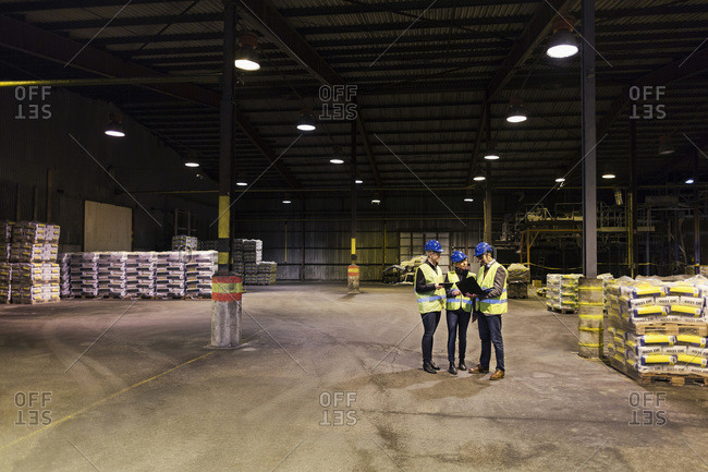 Manual workers using technologies in cement warehouse