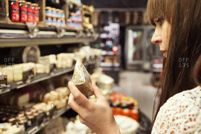 Woman analyzing cheese in supermarket