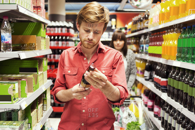 Man reading label on bottle while shopping in supermarket