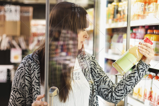 Young woman reading label on juice bottle at refrigerated section in supermarket