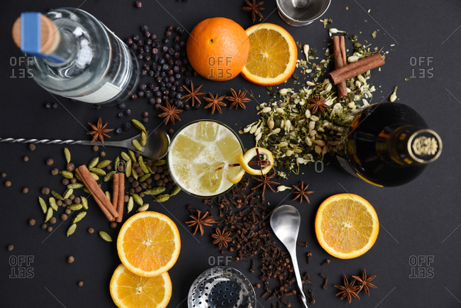 Spiced orange cocktail ingredients arranged on a black background