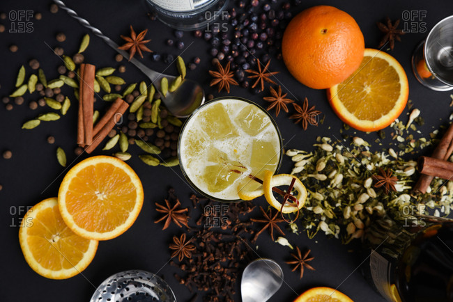 Overhead view of a spiced orange cocktail surrounded by the ingredients