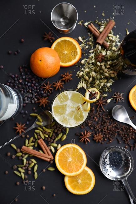 Spice orange cocktail ingredients arranged around a drink