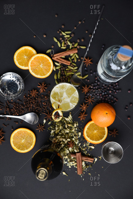 Overhead view of a frothy orange spiced cocktail surrounded by the ingredients
