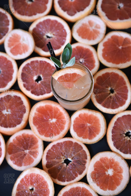 Overhead view of fresh squeezed grapefruit juice on a background of grapefruit slices