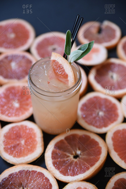 View of pink grapefruit juice on a background of slices of grapefruit