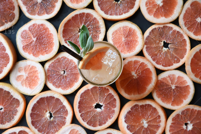 Overhead of a glass of fresh squeezed grapefruit juice resting on a background of slices of grapefruit
