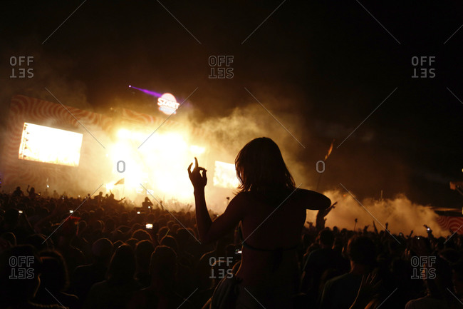 Budapest, Hungary - August 10, 2013: Woman sitting on a friend's shoulders dances at a concert at night